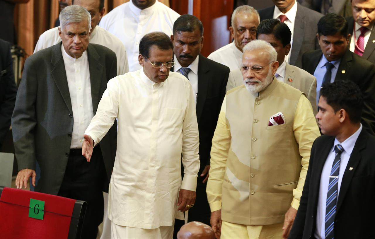 Indian Prime Minister Narendra Modi, second right, arrives at UN celebration ceremony of Vesak or Buddha Purnima with Sri Lankan President Maithripala Sirisena, second left, and Sri Lankan Prime Minister Ranil Wickremesinghe, left, in Colombo, Sri Lanka, Friday, May 12, 2017.
