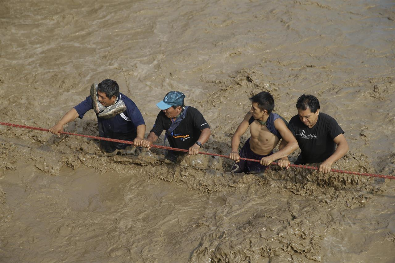 Men hold onto a rope as they wade through flood waters towards safety in Lima, Peru, Friday, March 17, 2017. Intense rains and mudslides over the past three days have wrought havoc around the Andean nation and caught residents in Lima, a desert city of 10 million where it almost never rains, by surprise.