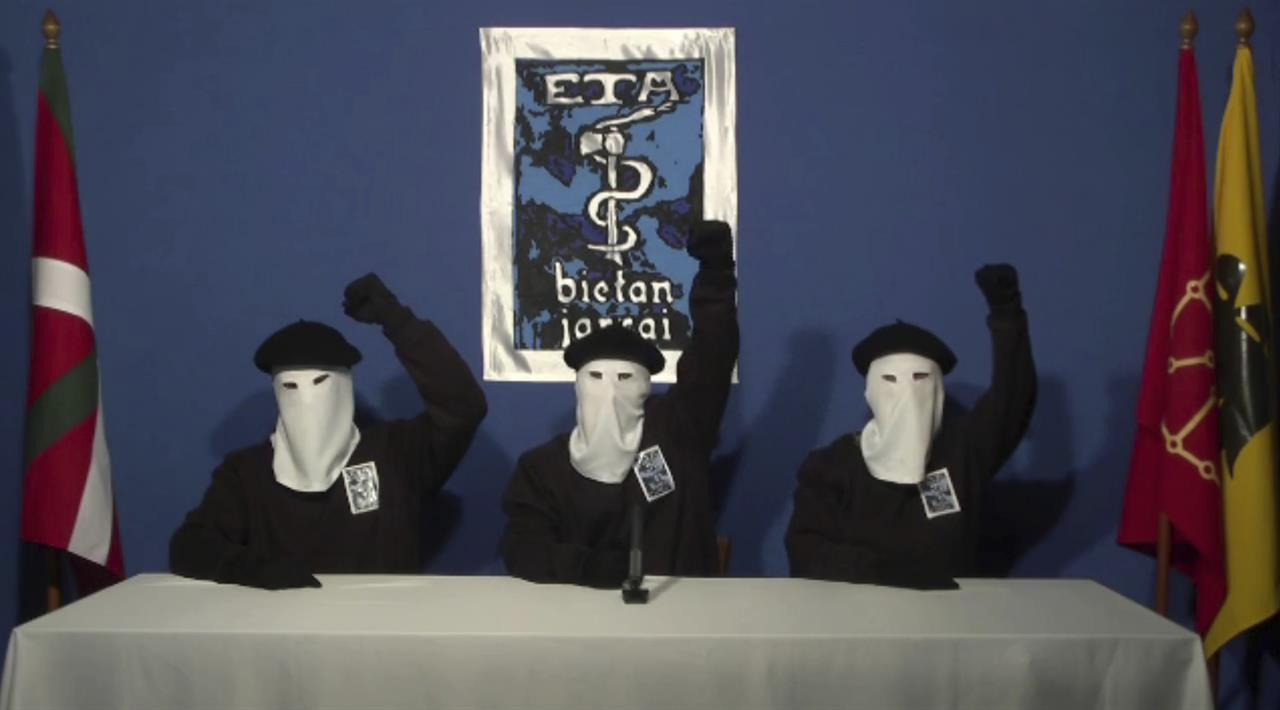 In this file image made from video provided on Oct. 20, 2011, masked members of the Basque separatist group ETA hold up their fists in unison following a news conference at an unknown location. Spanish media are reporting that ETA are set to announce Friday March 17, 2017 its new initiative to lay down weapons aimed at speeding the stalled process of disbanding.