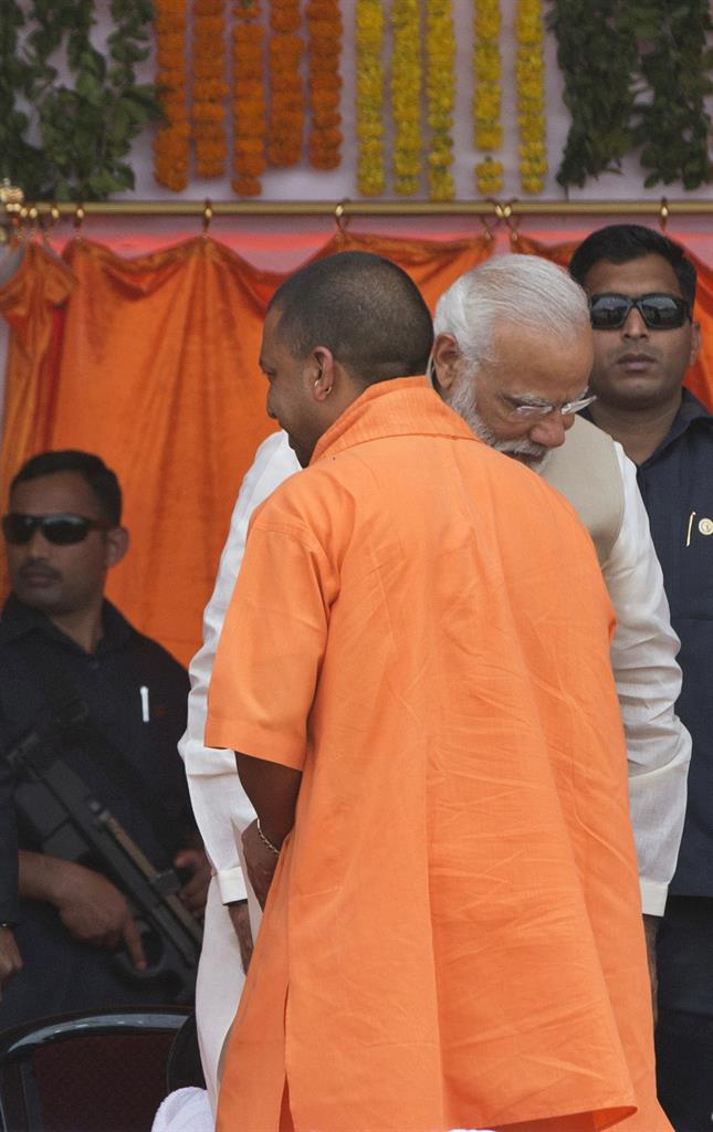 Security men guard behind Indian Prime Minister Narendra Modi, middle, during the swearing in of Yogi Adityanath, back to camera as Uttar Pradesh state chief minister in Lucknow, India, Sunday, March 19, 2017.