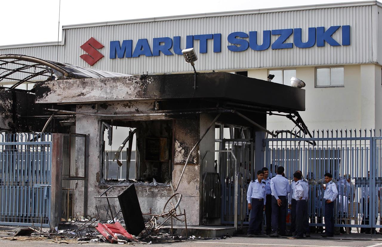 In this July 19, 2012, file photo, security guards stand near a burnt down reception block of Maruti Suzuki factory in Manesar, near New Delhi, India. A court in north India has sentenced 13 factory workers to life imprisonment for taking part in violence at the country's largest automobile factory that led to the death of a manager nearly five years ago.