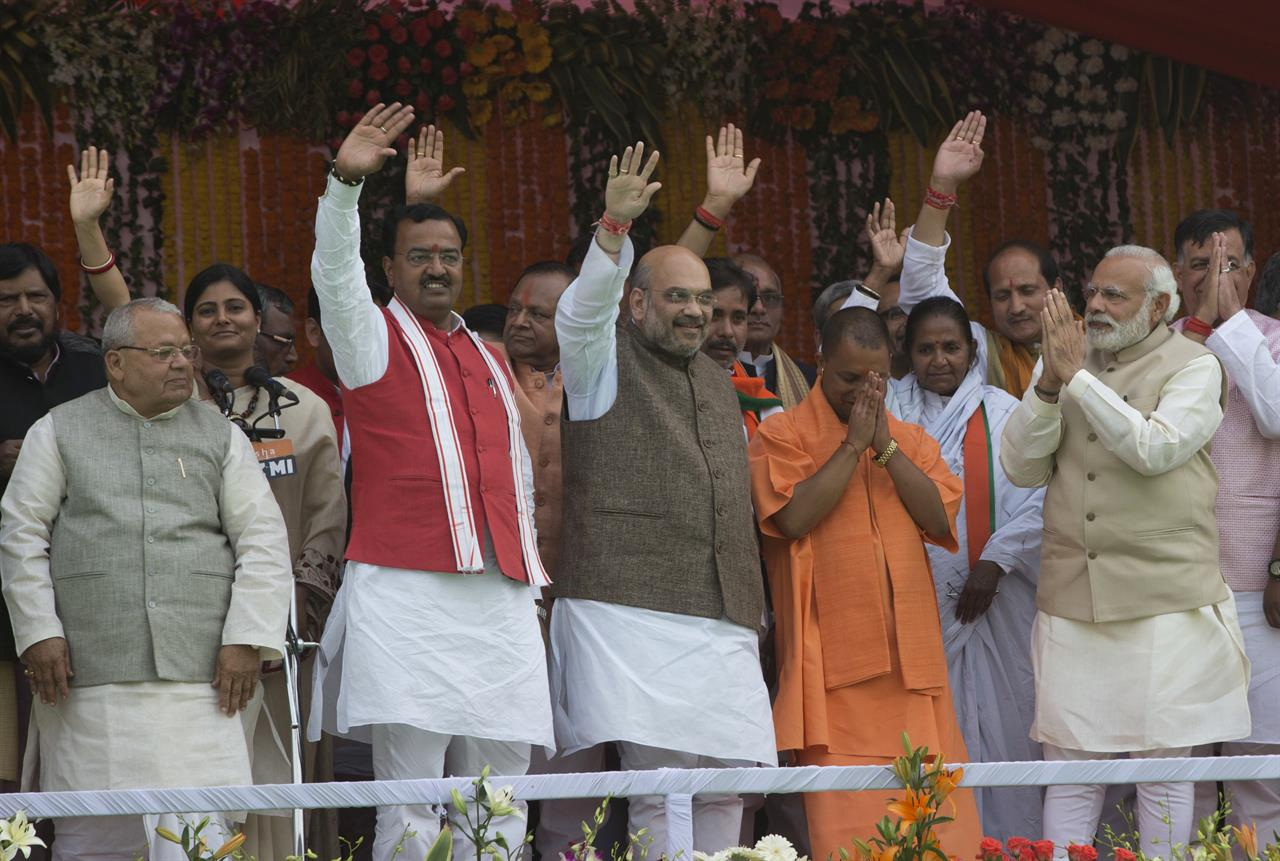 Indian Prime Minister Narendra Modi, second right and Yogi Adityanath, in saffron robes, greet with folded hands as Bharatiya Janata Party president Amit Shah, center and others wave to the audience after Adityanath was sworn in as Uttar Pradesh state chief minister in Lucknow, India, Sunday, March 19, 2017.