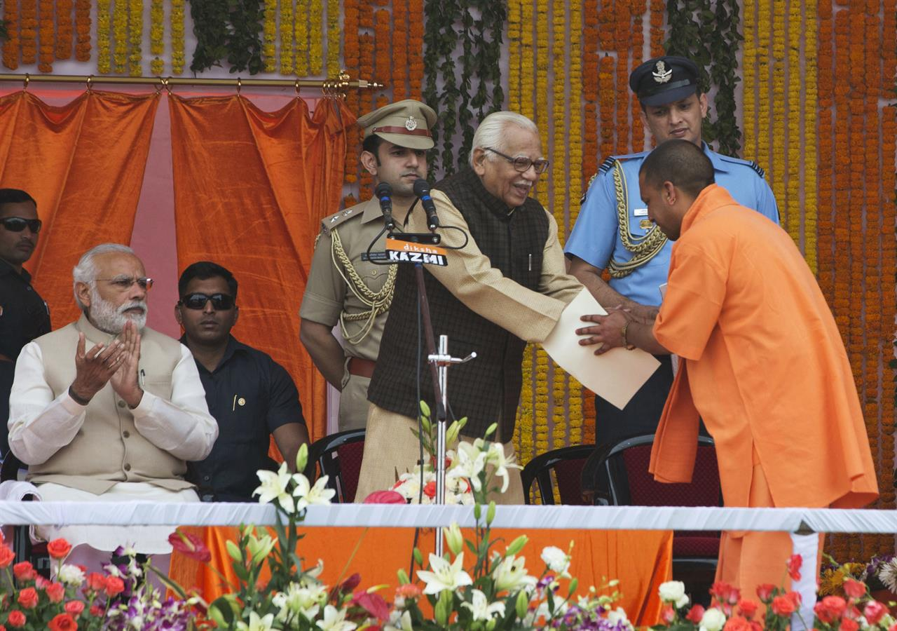 Indian Prime Minister Narendra Modi, left, watches as Yogi Adityanath, standing right greets Governor Ram Naik, after taking oath as Uttar Pradesh state chief minister in Lucknow, India, Sunday, March 19, 2017.