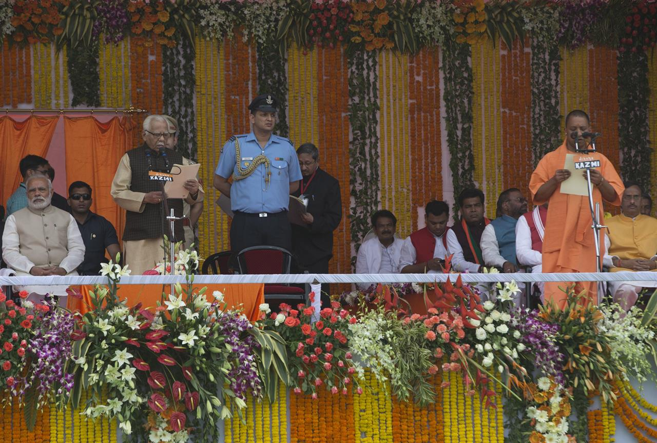 Indian Prime Minister Narendra Modi, left watches as Yogi Adityanath, standing right takes oath as Uttar Pradesh state chief minister in Lucknow, India, Sunday, March 19, 2017. Administering the oath of office is state Governor Ram Naik, standing left.