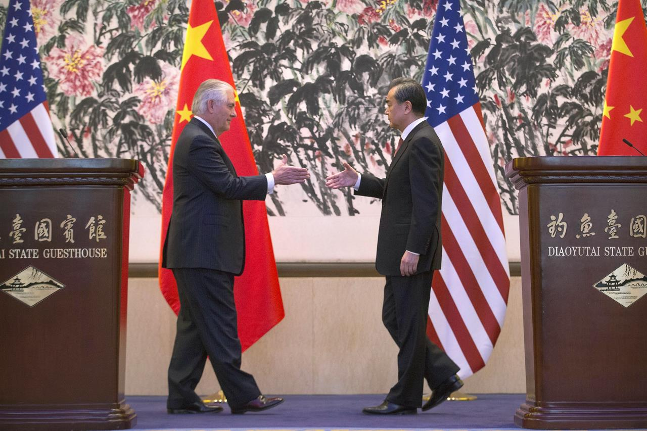 In this Saturday, March 18, 2017 photo, U.S. Secretary of State Rex Tillerson, left, and Chinese Foreign Minister Wang Yi reach to shake hands at the end of a joint press conference following their meeting at the Diaoyutai State Guesthouse in Beijing, China. Tillerson pushed for closer China-U.S. cooperation on dealing with North Korea's nuclear program in his first face-to-face talks Saturday with leading Chinese diplomats.