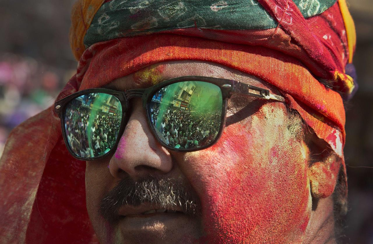 In this Monday, March 13, 2017 photo, Indians dancing during the Holi celebrations are reflected on the sunglass of a man whose face is smeared in colors in Gauhati, India. The festival also heralds the arrival or spring.