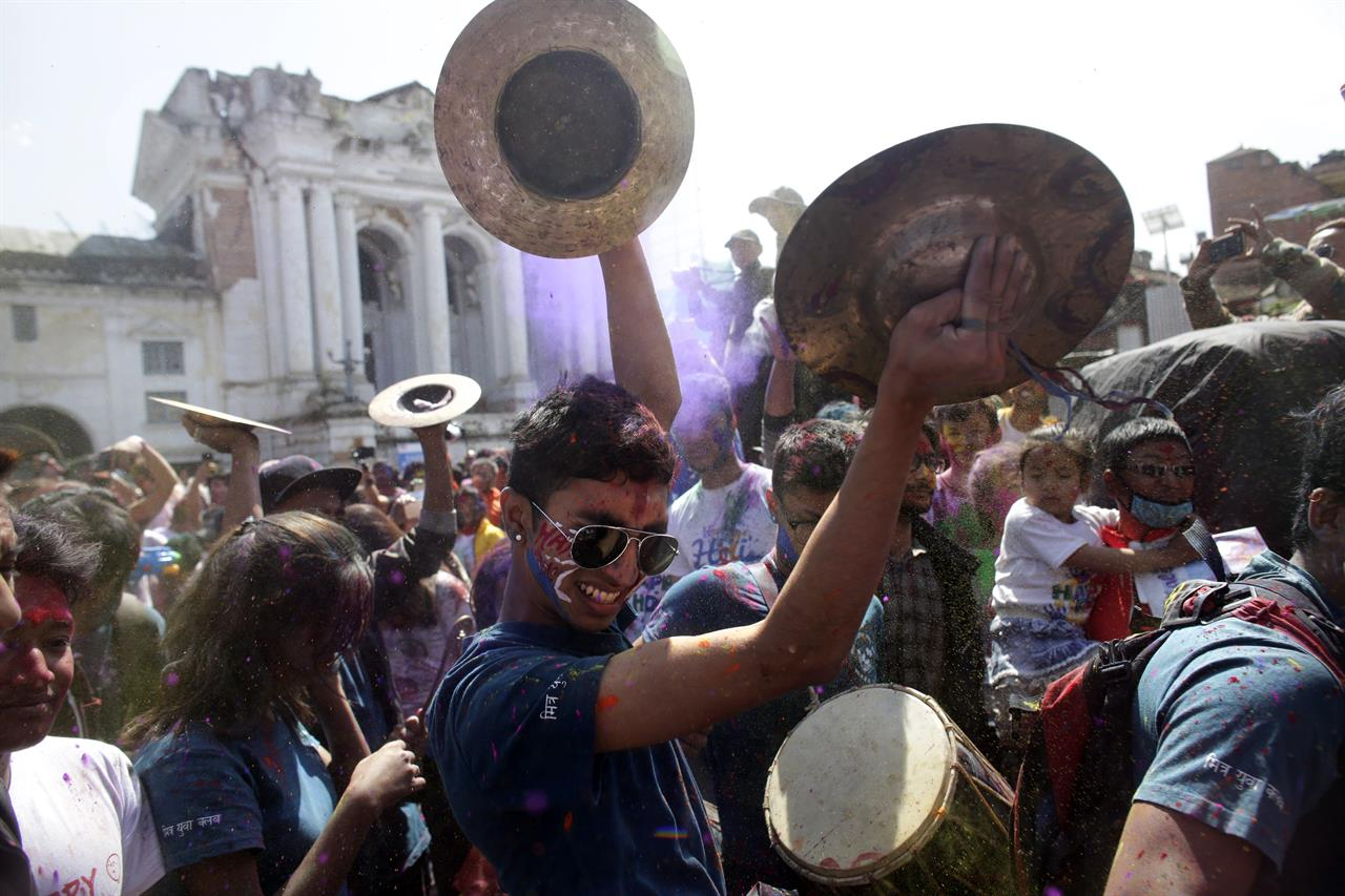 In this Sunday, March 12, 2017 photo, a Nepalese man plays a traditional instrument as people gather for Holi festivities at the Basantapur Durbar Square in Kathmandu, Nepal. The Holi festival marks the advent of spring.