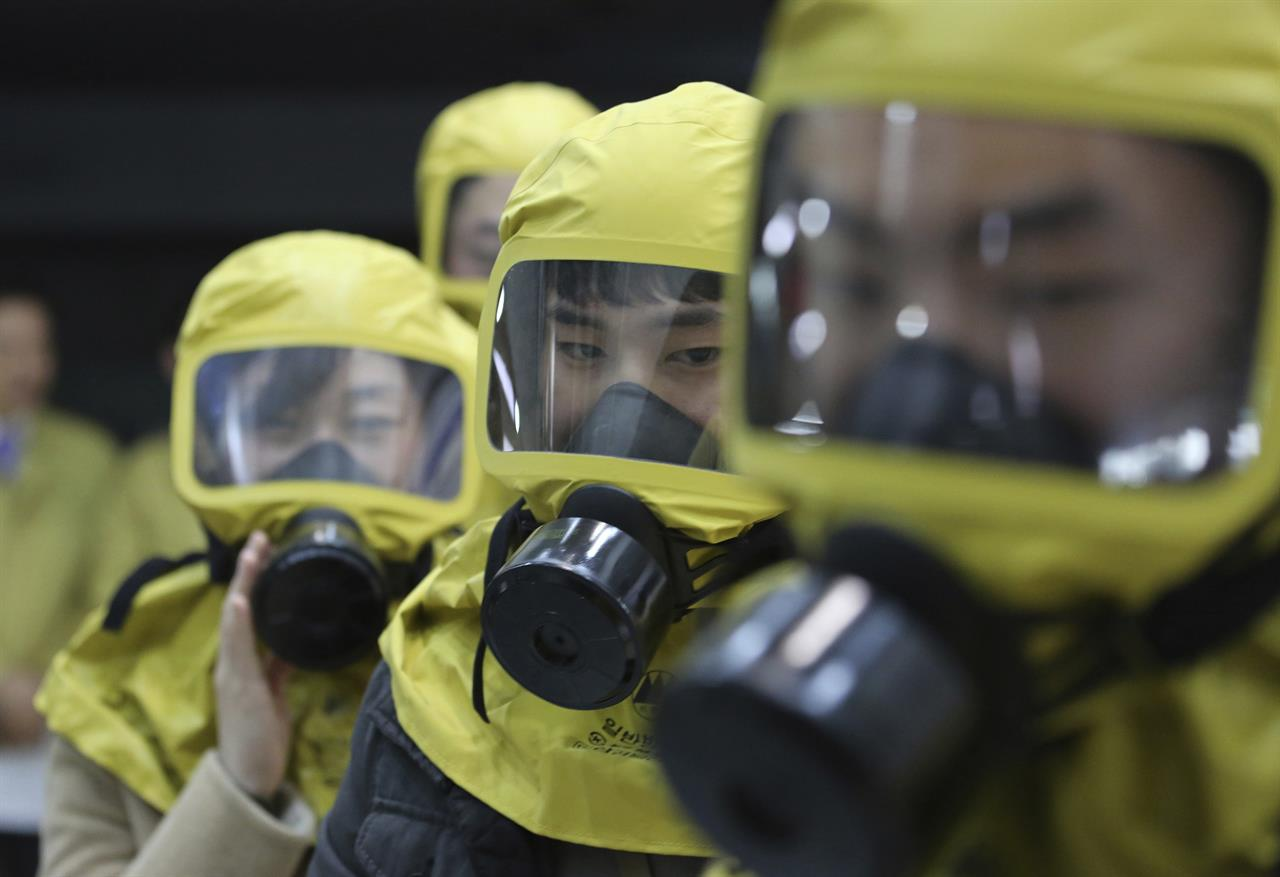 In this Wednesday, March 15, 2017 photo, South Korean government officials wearing gas masks attend a civil defense drill against possible North Korea's chemical attack at their office in Seoul, South Korea. A nationwide civil defense drill took place Wednesday preparing for possible terror, natural disaster and sudden air attack by North Korea.