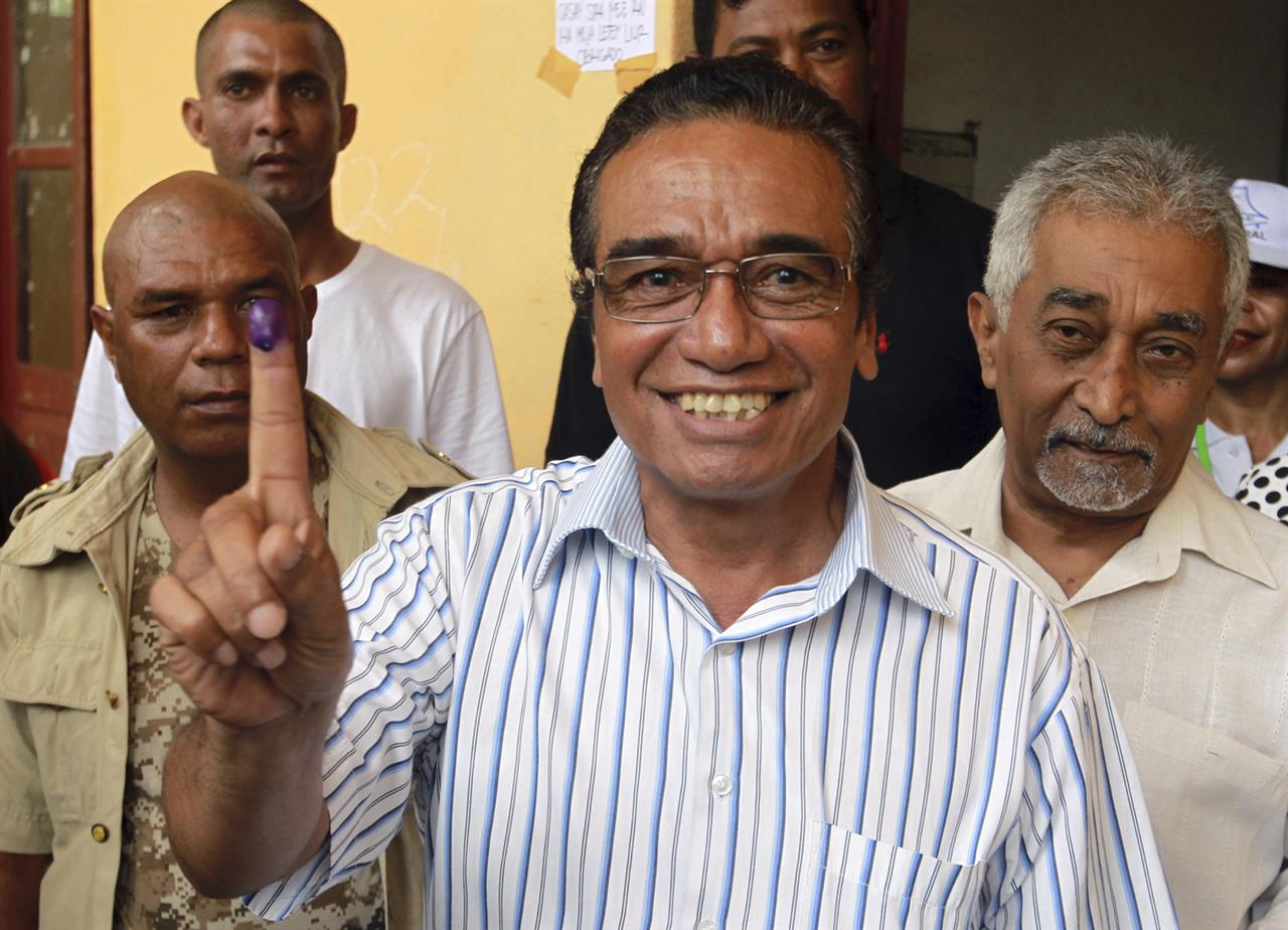 "Fretilin Party leader Francisco ""Lu-Olo"" Guterres, center, shows his inked finger after giving his vote during the presidential election at a polling station in Dili, East Timor, Monday, March 20, 2017. East Timorese went to vote Monday in the first presidential election since the U.N. officially ended the peacekeeping mission in the country in 2012."