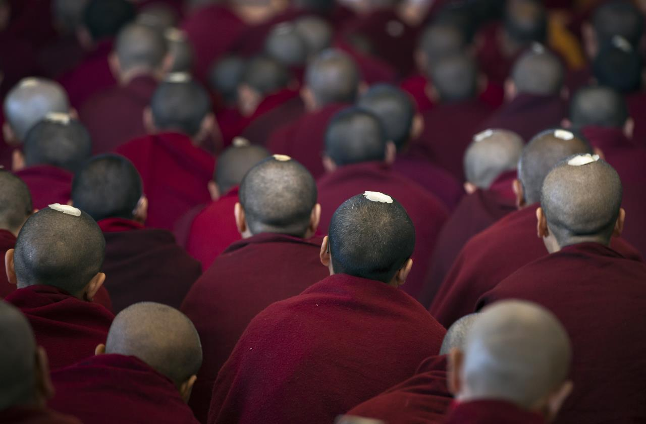 In this Tuesday, March 14, 2017 photo, exile Tibetan Buddhist monks have ceremonial seeds on their shaven heads as they listen to a religious talk by their spiritual leader the Dalai Lama at the Tsuglakhang temple in Dharmsala, India. The two-day talk ended Tuesday.