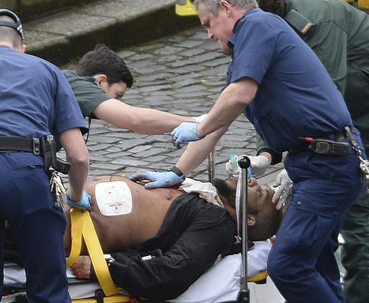 "An attacker is treated by emergency services outside the Houses of Parliament London, Wednesday, March 22, 2017. London police say they are treating a gun and knife incident at Britain's Parliament ""as a terrorist incident until we know otherwise."" The Metropolitan Police says in a statement that the incident is ongoing. It is urging people to stay away from the area. Officials say a man with a knife attacked a police officer at Parliament and was shot by officers. Nearby, witnesses say a vehicle struck several people on the Westminster Bridge."