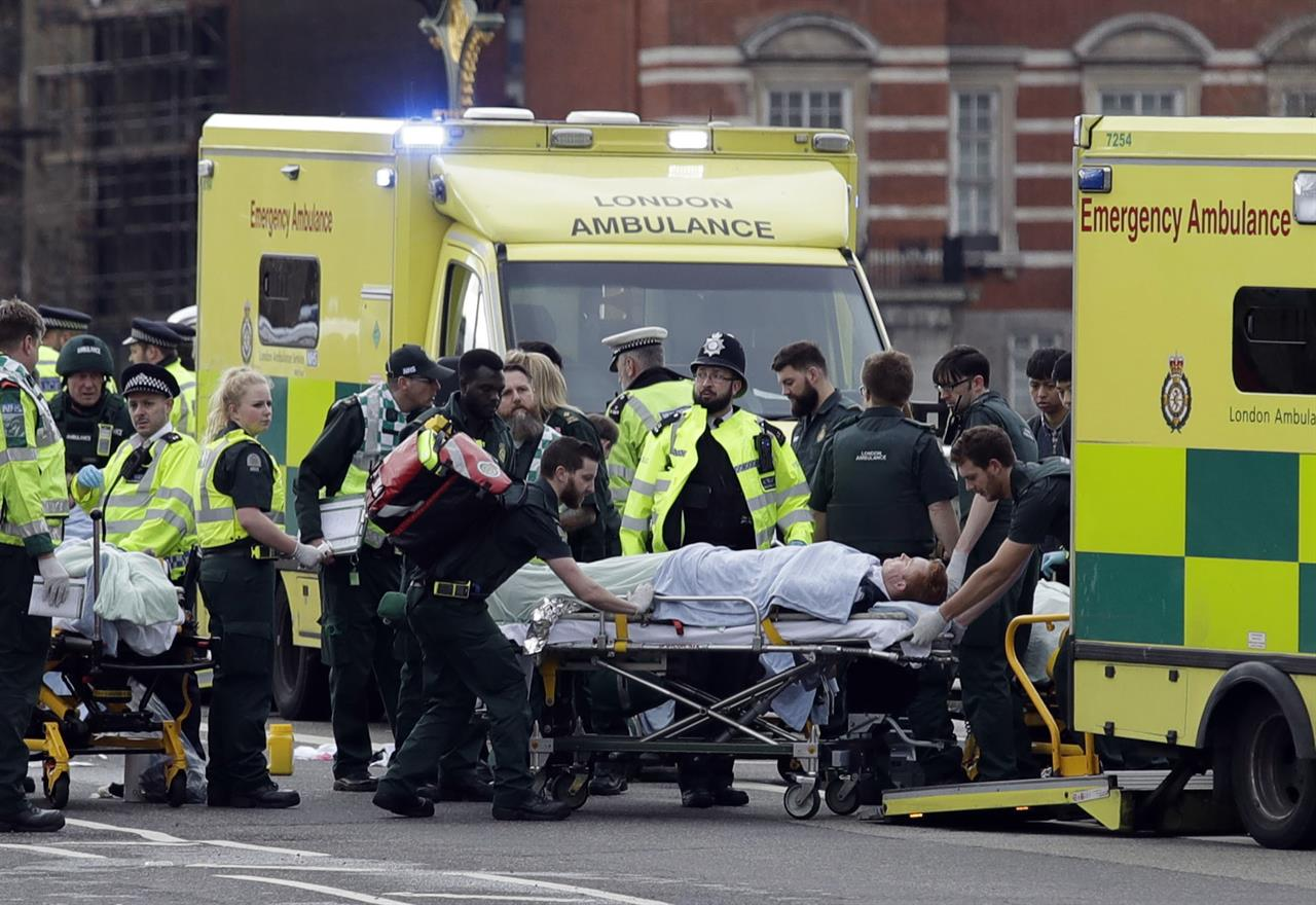 "Emergency services transport an injured person to an ambulance, close to the Houses of Parliament in London, Wednesday, March 22, 2017. London police say they are treating a gun and knife incident at Britain's Parliament ""as a terrorist incident until we know otherwise."" The Metropolitan Police says in a statement that the incident is ongoing. Officials say a man with a knife attacked a police officer at Parliament and was shot by officers. Nearby, witnesses say a vehicle struck several people on the Westminster Bridge."