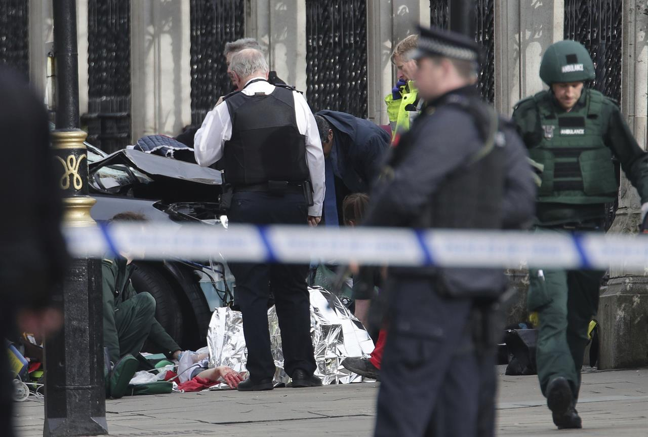 "Emergency personnel tend to an injured person close to the Palace of Westminster, London, Wednesday, March 22, 2017. London police say officers called to a 'firearms incident' on Westminster Bridge, near Parliament. The leader of Britain's House of Commons says a man has been shot by police at Parliament. David Liddington also said there were ""reports of further violent incidents in the vicinity."" London's police said officers had been called to a firearms incident on Westminster Bridge, near the parliament. Britain's MI5 says it is too early to say if the incident is terror-related."