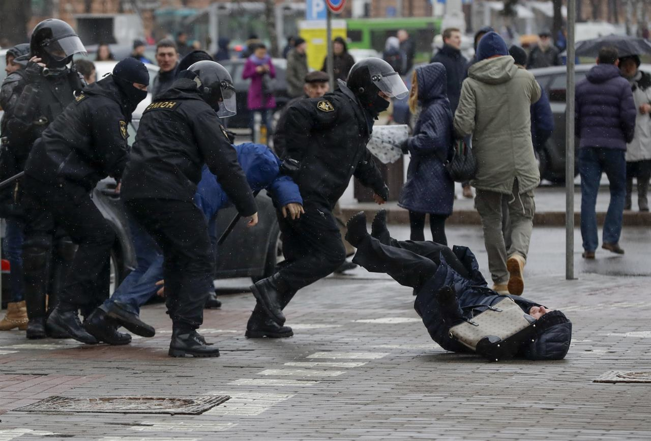 Belarus police push a woman down while detaining an activist during an opposition rally in Minsk, Belarus, Saturday, March 25, 2017. A cordon of club-wielding police blocked the demonstrators' movement along Minsk's main avenue near the Academy of Science. Hulking police detention trucks were deployed in the city center.