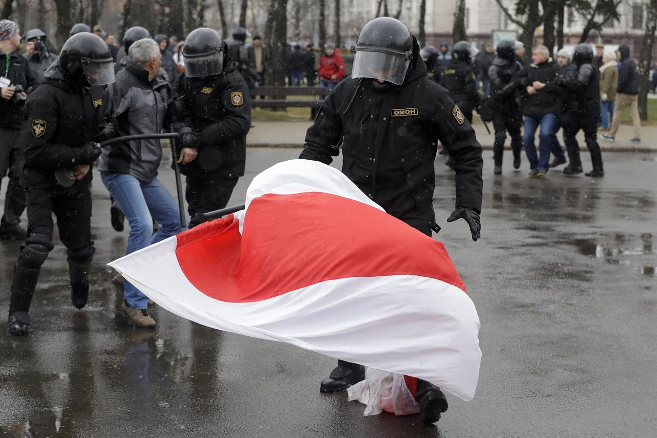 A Belarus policeman tries to crumple an opposition flag as other detain a protester during an opposition rally in Minsk, Belarus, Saturday, March 25, 2017. A cordon of club-wielding police blocked the demonstrators' movement along Minsk's main avenue near the Academy of Science. Hulking police detention trucks were deployed in the city center.