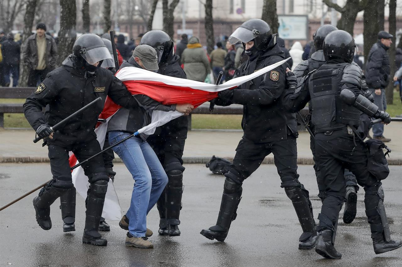 Belarus police detain a protester with an opposition flag during an opposition rally in Minsk, Belarus, Saturday, March 25, 2017. A cordon of club-wielding police blocked the demonstrators' movement along Minsk's main avenue near the Academy of Science. Hulking police detention trucks were deployed in the city center.