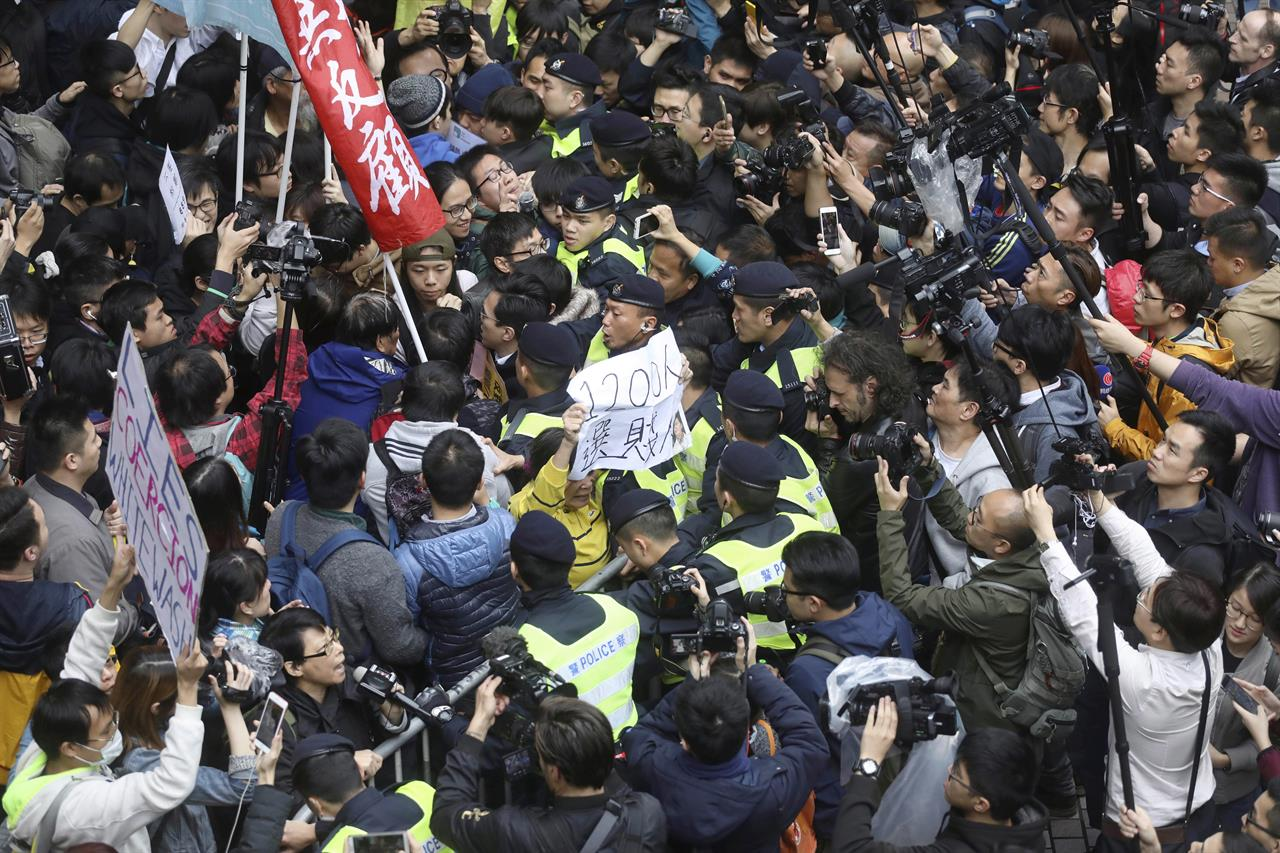 "Protesters scuffle with police officers during a protest against the chief executive election in Hong Kong, Sunday, March 26, 2017. A committee dominated by pro-Beijing elites is casting ballots Sunday to choose Hong Kong's next leader in the first such vote since 2014's huge pro-democracy protests. The system has been criticized by pro-democracy activists as a ""fake election""."