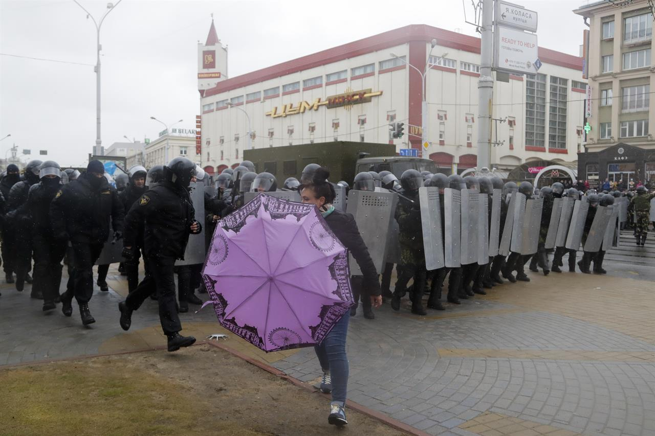 A woman runs out as Belarus police block a street during an opposition rally in Minsk, Belarus, Saturday, March 25, 2017. A cordon of club-wielding police blocked the demonstrators' movement along Minsk's main avenue near the Academy of Science. Hulking police detention trucks were deployed in the city center.
