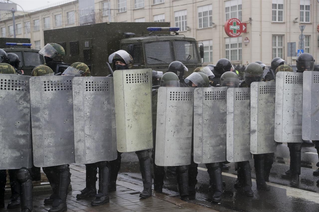 Belarus police block a street during an opposition rally in Minsk, Belarus, Saturday, March 25, 2017. A cordon of club-wielding police blocked the demonstrators' movement along Minsk's main avenue near the Academy of Science. Hulking police detention trucks were deployed in the city center.
