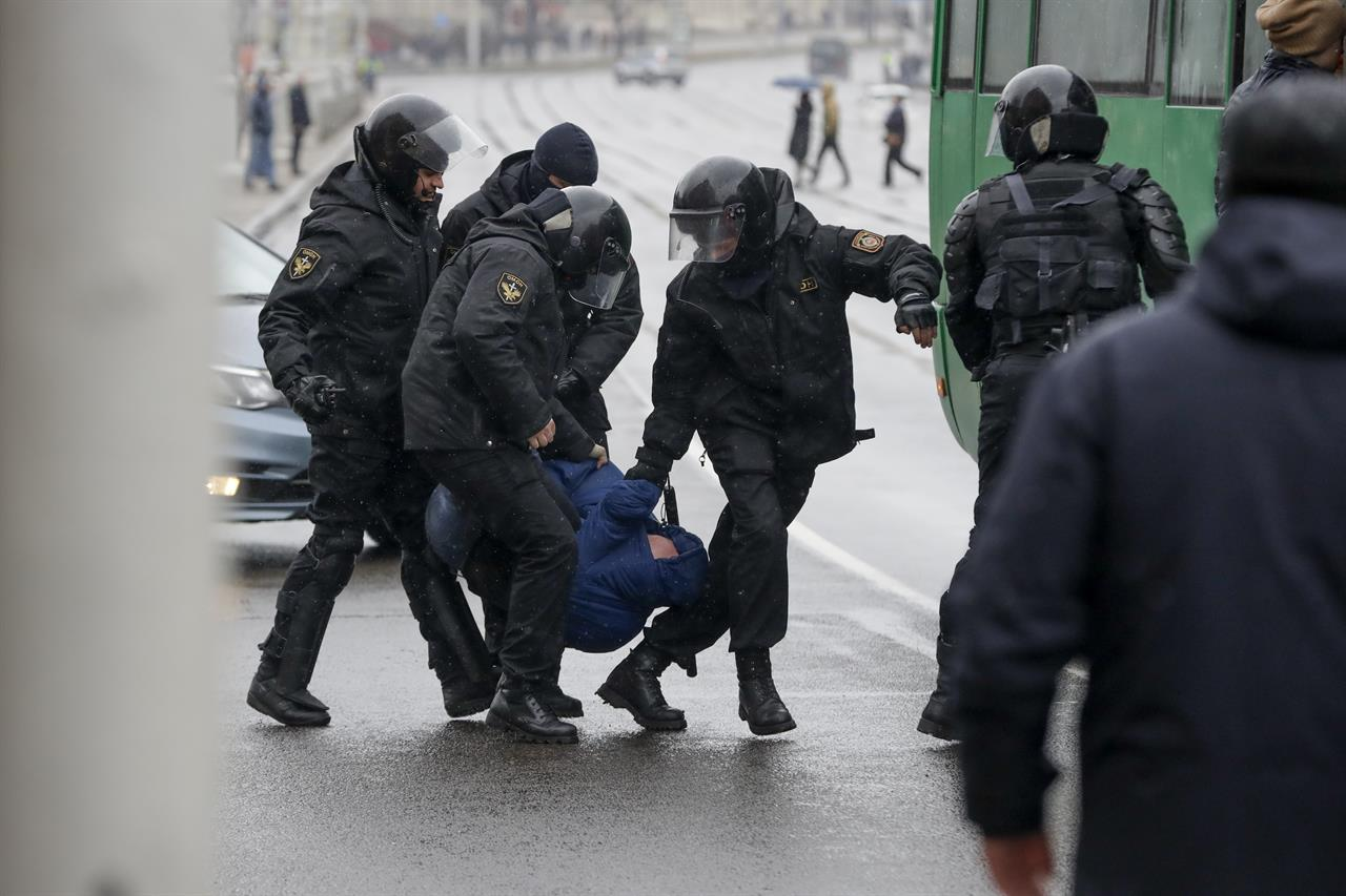 Belarus police detain an activist during an opposition rally in Minsk, Belarus, Saturday, March 25, 2017. A cordon of club-wielding police blocked the demonstrators' movement along Minsk's main avenue near the Academy of Science. Hulking police detention trucks were deployed in the city center.