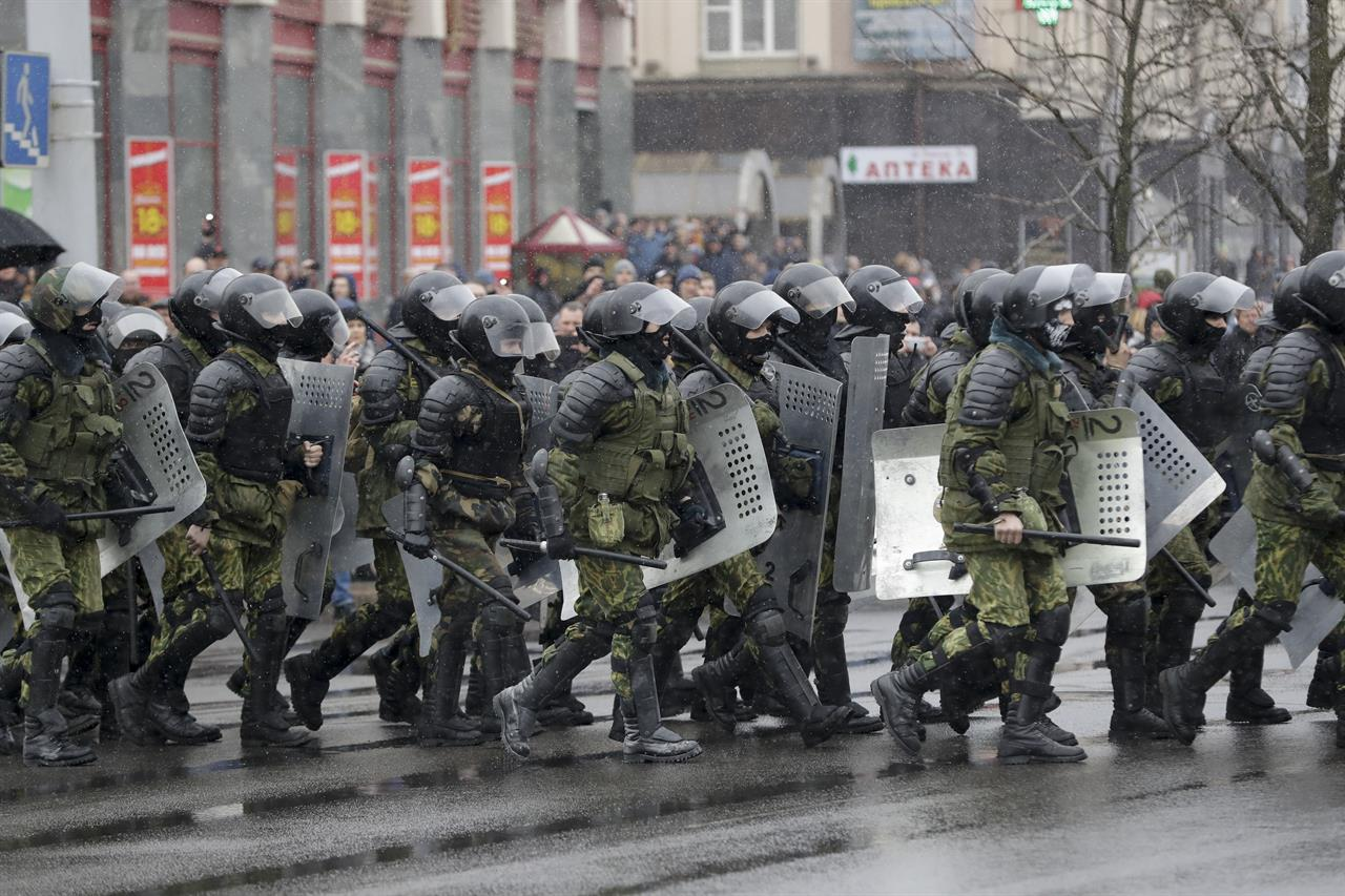 Belarus police walk to block a street during an opposition rally in Minsk, Belarus, Saturday, March 25, 2017. A cordon of club-wielding police blocked the demonstrators' movement along Minsk's main avenue near the Academy of Science. Hulking police detention trucks were deployed in the city center.