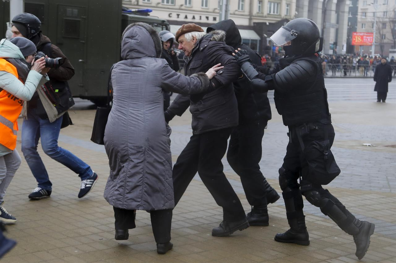 Belarus police detain a man, as a woman tries to defend him during an opposition rally in Minsk, Belarus, Saturday, March 25, 2017. A cordon of club-wielding police blocked the demonstrators' movement along Minsk's main avenue near the Academy of Science. Hulking police detention trucks were deployed in the city center.