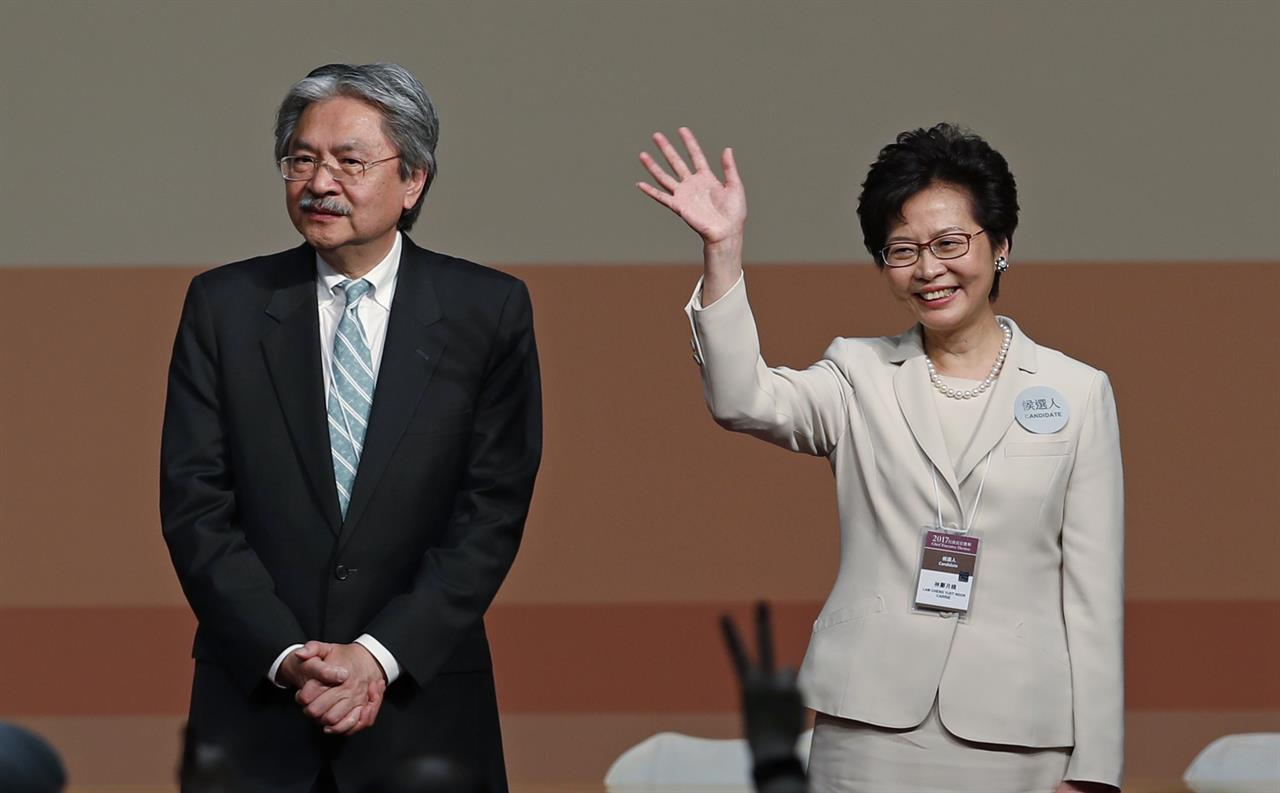 Former Hong Kong Chief Secretary Carrie Lam, right, waves after she declared her victory in the chief executive election of Hong Kong while her rival candidate former Financial Secretary John Tsang stands by her in Hong Kong, Sunday, March 26, 2017. The candidate favored by China's Communist leadership was chosen as Hong Kong's new leader on Sunday, in the first such vote since huge pro-democracy protests erupted over the city's election system in 2014.