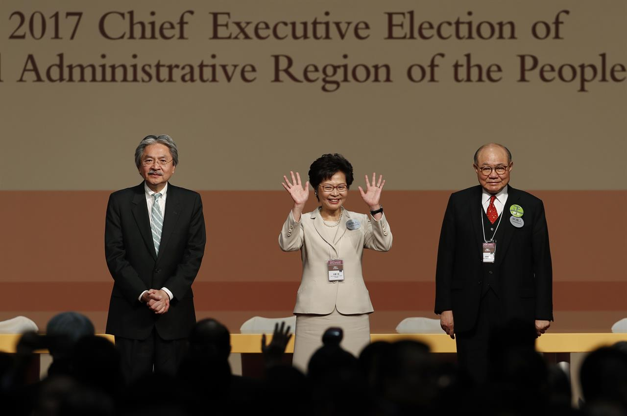 Former Hong Kong Chief Secretary Carrie Lam, center, waves as she declares her victory in the chief executive election of Hong Kong while former Financial Secretary John Tsang, left, and retired judge Woo Kwok-hing stand with her in Hong Kong, Sunday, March 26, 2017. A Hong Kong committee has chosen the government's former No. 2 official Lam to be the semiautonomous Chinese city's next leader.