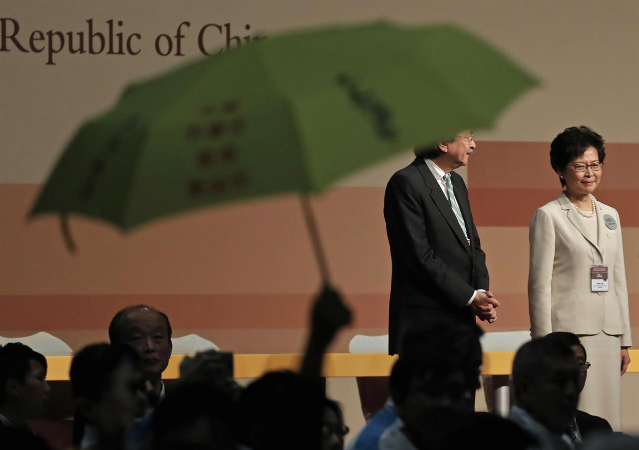 A protester raises an umbrella to protest former Hong Kong Chief Secretary Carrie Lam, right, after she declared her victory in the chief executive election of Hong Kong while standing with former Financial Secretary John Tsang in Hong Kong, Sunday, March 26, 2017. A Hong Kong committee has chosen the government's former No. 2 official Lam to be the semiautonomous Chinese city's next leader.