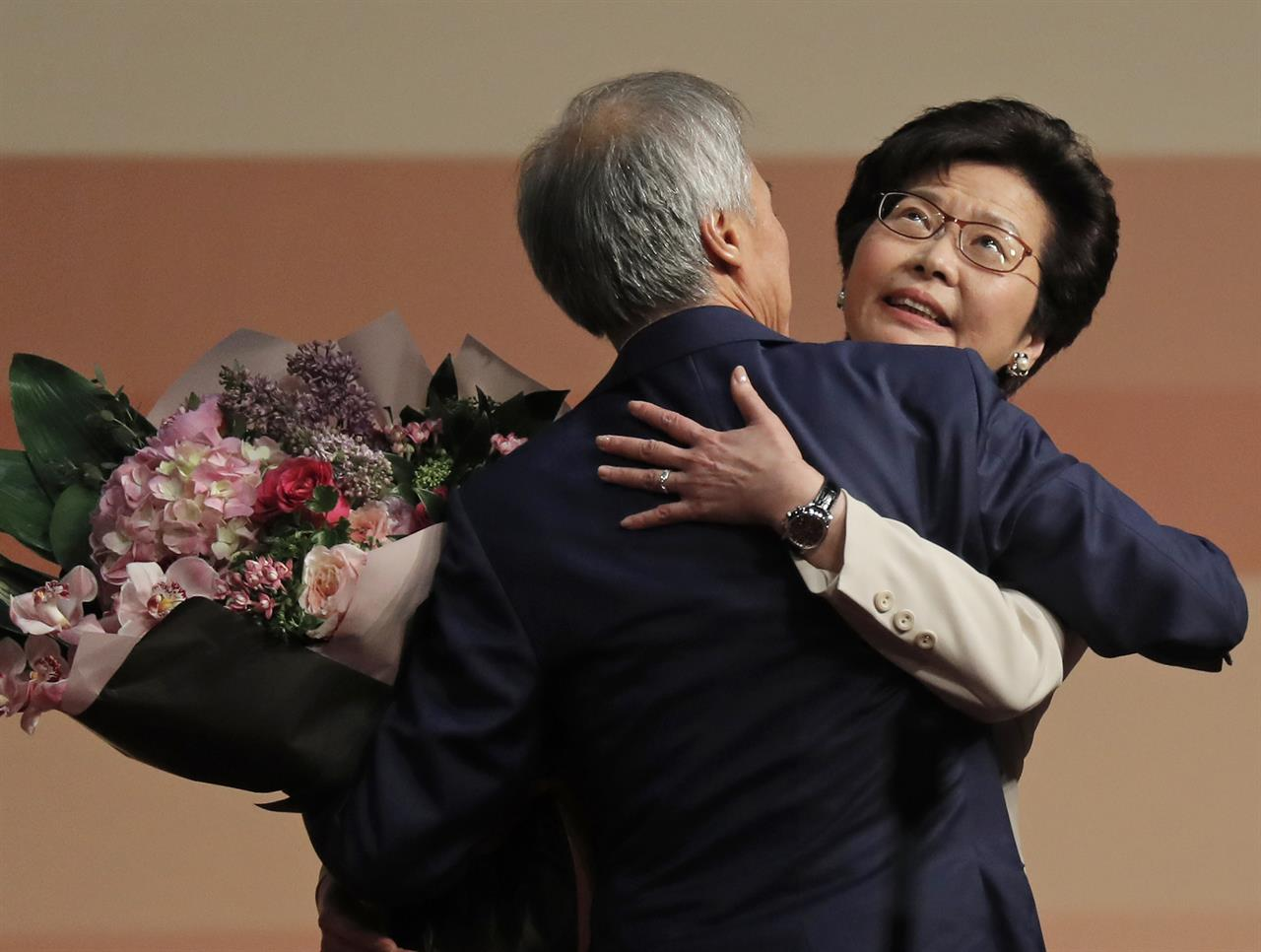 Former Hong Kong Chief Secretary Carrie Lam, right, is hugged by her husband Lam Siu-por after declaring her victory in the chief executive election of Hong Kong in Hong Kong, Sunday, March 26, 2017. A committee dominated by pro-Beijing elites chose Hong Kong's next leader Sunday in the first vote since huge pro-democracy protests erupted over the election system in 2014.