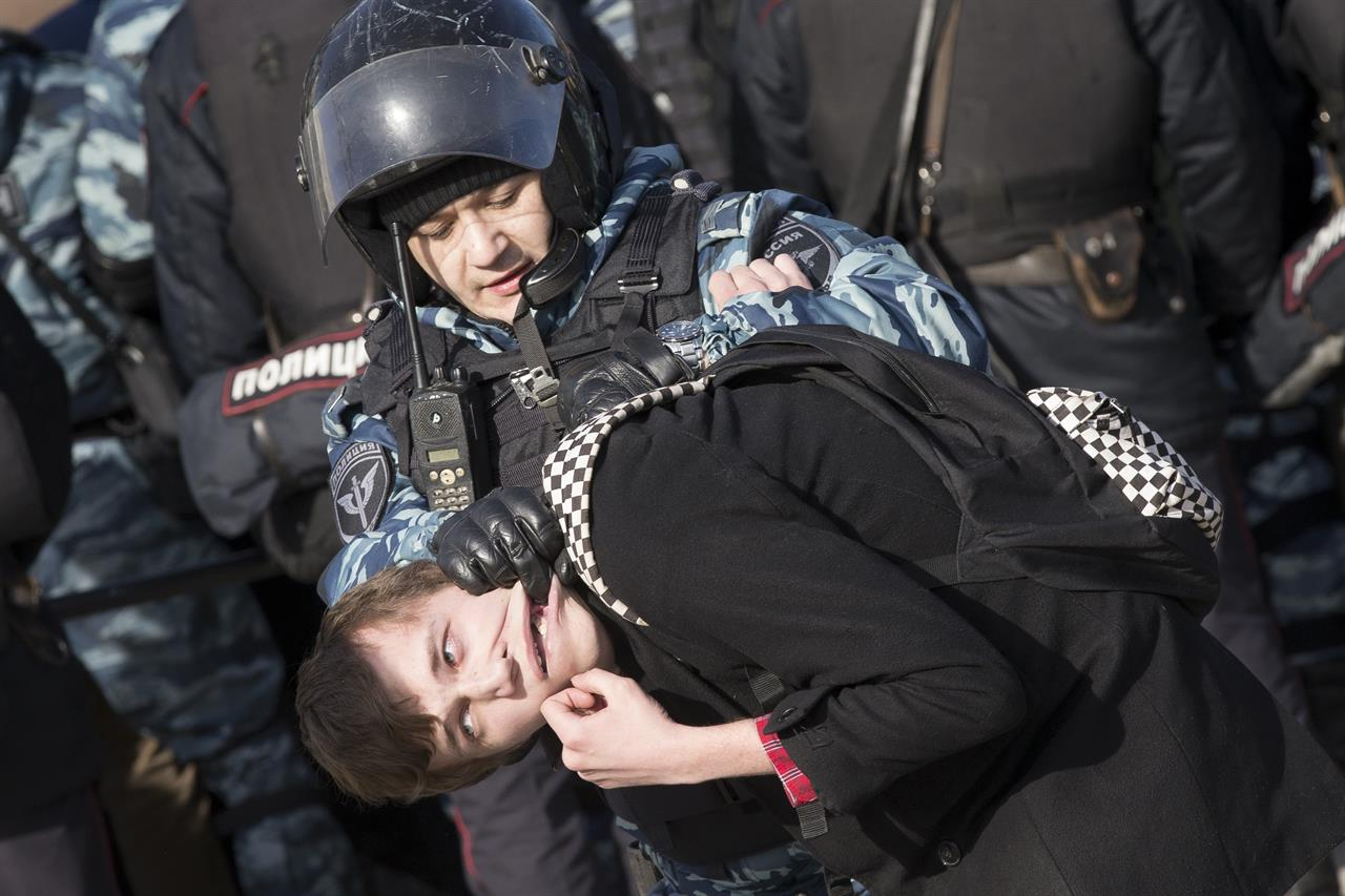 Police detain a protester in downtown Moscow, Russia, Sunday, March 26, 2017. Thousands of people crowded into Moscow's Pushkin Square on Sunday for an unsanctioned protest against the Russian government, the biggest gathering in a wave of nationwide protests that were the most extensive show of defiance in years.