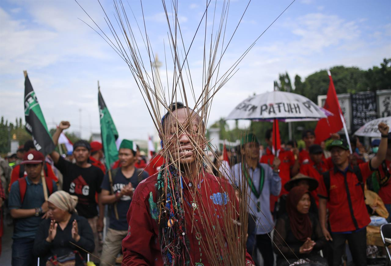 In this Monday, March 20, 2017 photo, an activist has skewers wrapped around his head with rubber bands during a rally against the operation of a cement factory in Kendeng, West Java, outside the presidential palace in Jakarta, Indonesia. Kendeng farmers have battled against plans for the factory for years, saying it could taint their water. The factory is now more or less complete and the owner, state-owned PT Semen Indonesia, has said it would create jobs and boost the local economy.
