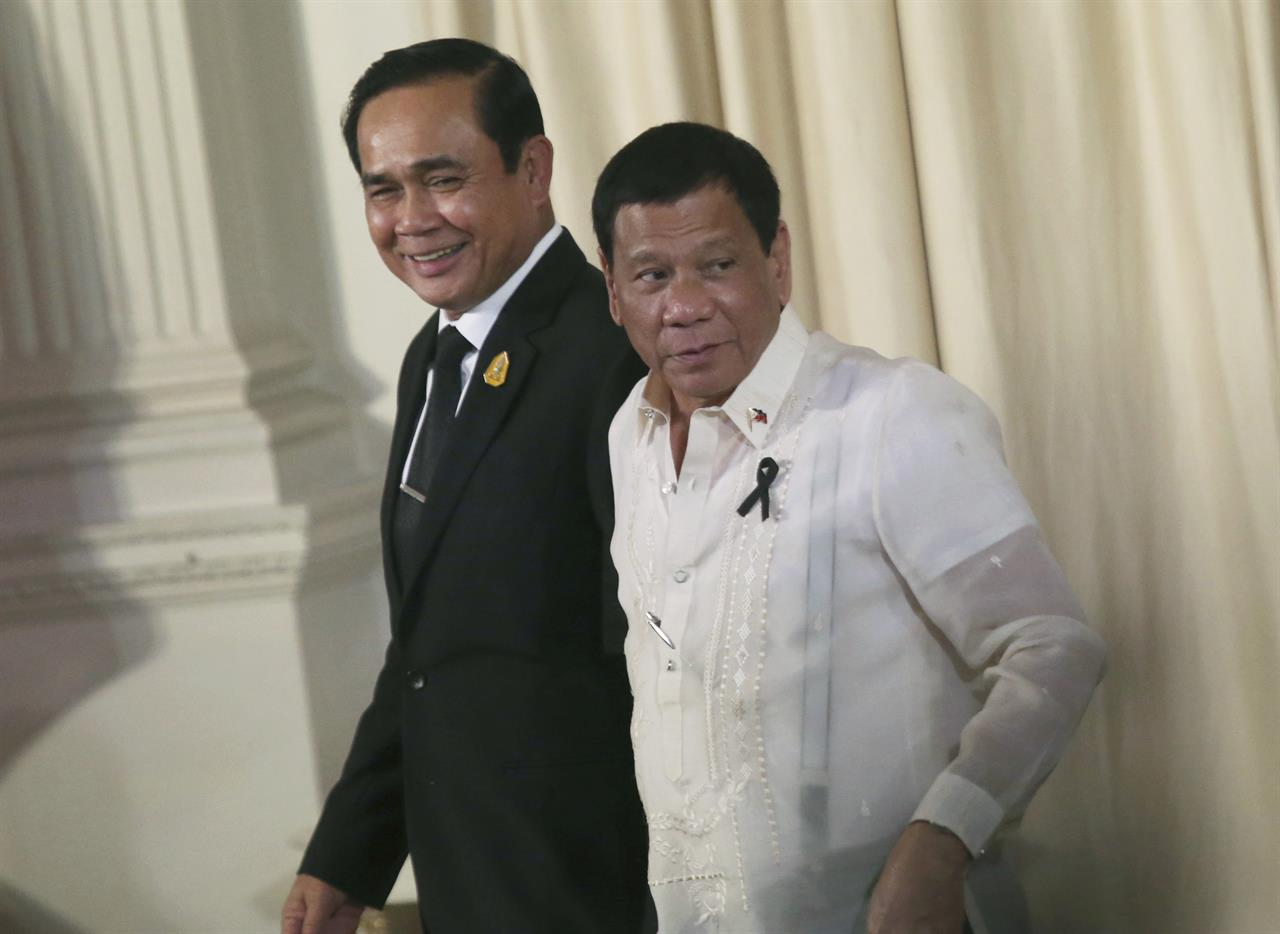 In this Tuesday, March 21, 2017 photo, Philippine President Rodrigo Duterte, right, and Thailand's Prime Minister Prayuth Chan-ocha walk together as they leave a joint press conference at the government house in Bangkok, Thailand. Duterte is in Thailand for a two-day visit rounding out his nine-country tour of southeast Asia.