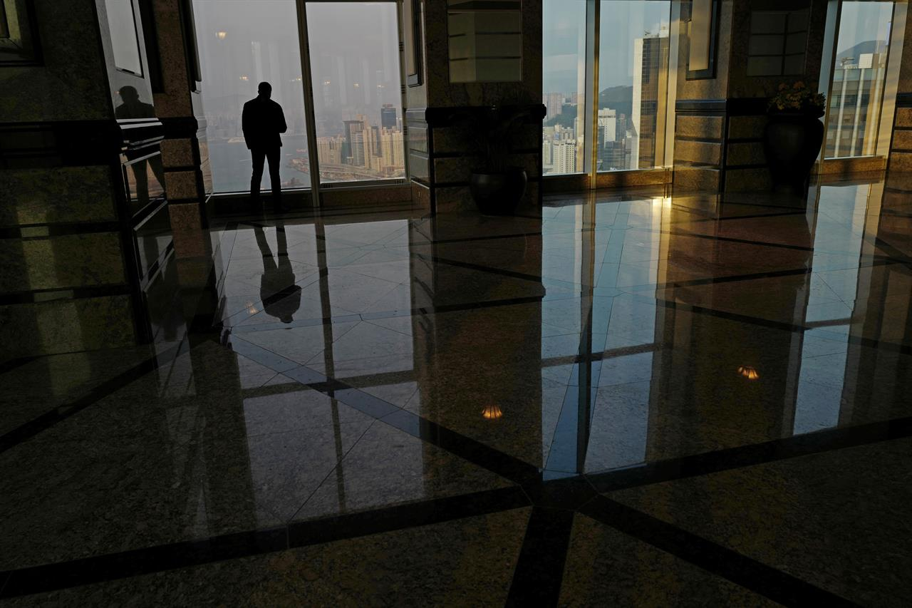In this Monday, March 20, 2017 photo, a man looks at the Victoria Harbour from a commercial building in Hong Kong. In the morning of Sunday, March 26, a select group of tycoons, business leaders, politicians and trade and industry group representatives will gather in a cavernous exhibition center to vote for the next leader of Hong Kong. Three candidates are on the ballot but there's little uncertainty about who the winner will be, with China's communist leaders already signaling early on their preference to the committee, which is stacked with pro-Beijing loyalists.