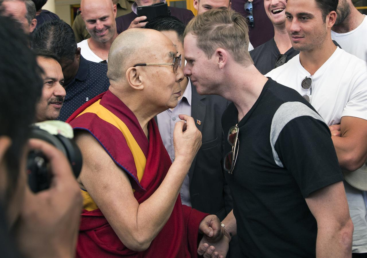 In this Friday, March 24, 2017 photo, Tibetan spiritual leader the Dalai Lama and Australian cricket team captain Steven Smith rub their noses during an interaction with the team at the Tsuglakhang temple in Dharmsala, India.