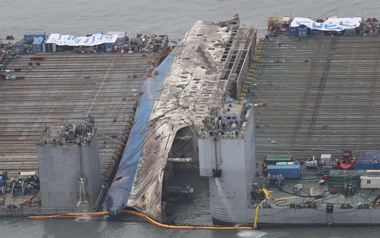 In this Friday, March 24, 2017 photo, the partially lifted sunken ferry Sewol, center, is ready for transport in waters off Jindo, South Korea. South Korean efforts to bring a sunken, 6,800-ton ferry back to land cleared an obstacle on Friday after divers cut off a vehicle ramp that had been dangling from the ship and hindering efforts to raise it.