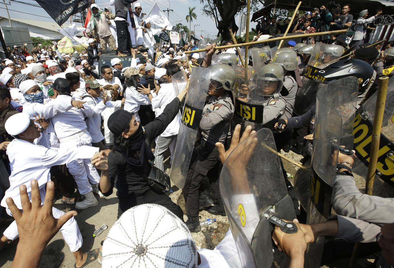 In this Friday, March 24, 2017 photo, police officers clash with Muslim hardliners during a protest against the construction of a Catholic church in Bekasi, Indonesia. Indonesian police fired tear gas to disperse the protesters as they tried to force their way into the Santa Clara church, which has been under construction since November.