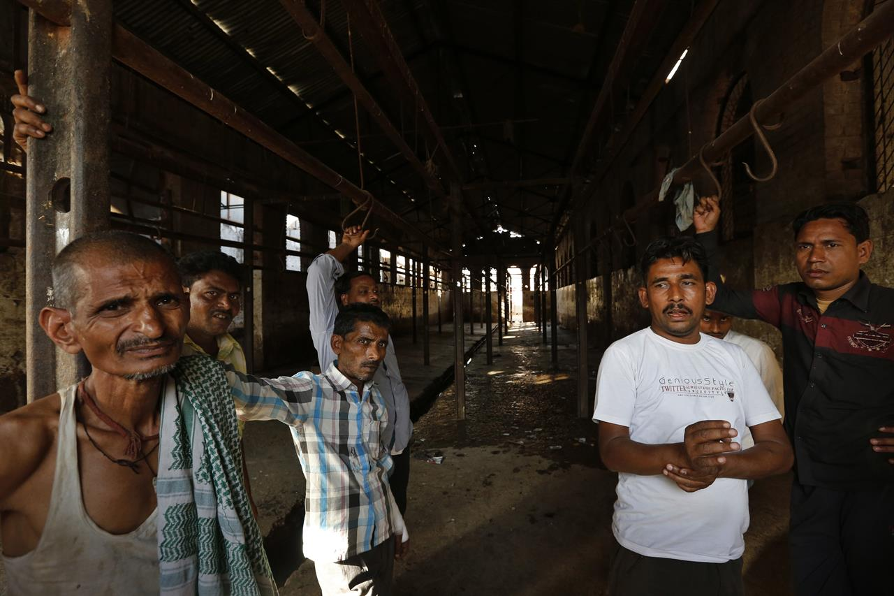 In this Sunday, March 26, 2017 photo, workers stand at a slaughter house where they used to work after the same was shutdown by authorities in Allahabad, India. India's most populous state is running out of meat. After the Hindu right-wing Bharatiya Janata Party came to power in Uttar Pradesh this month on the back of a resounding electoral victory and named a Hindu priest-cum-politician as the state's chief minister, the government began cracking down on illegal slaughterhouses and meat shops.