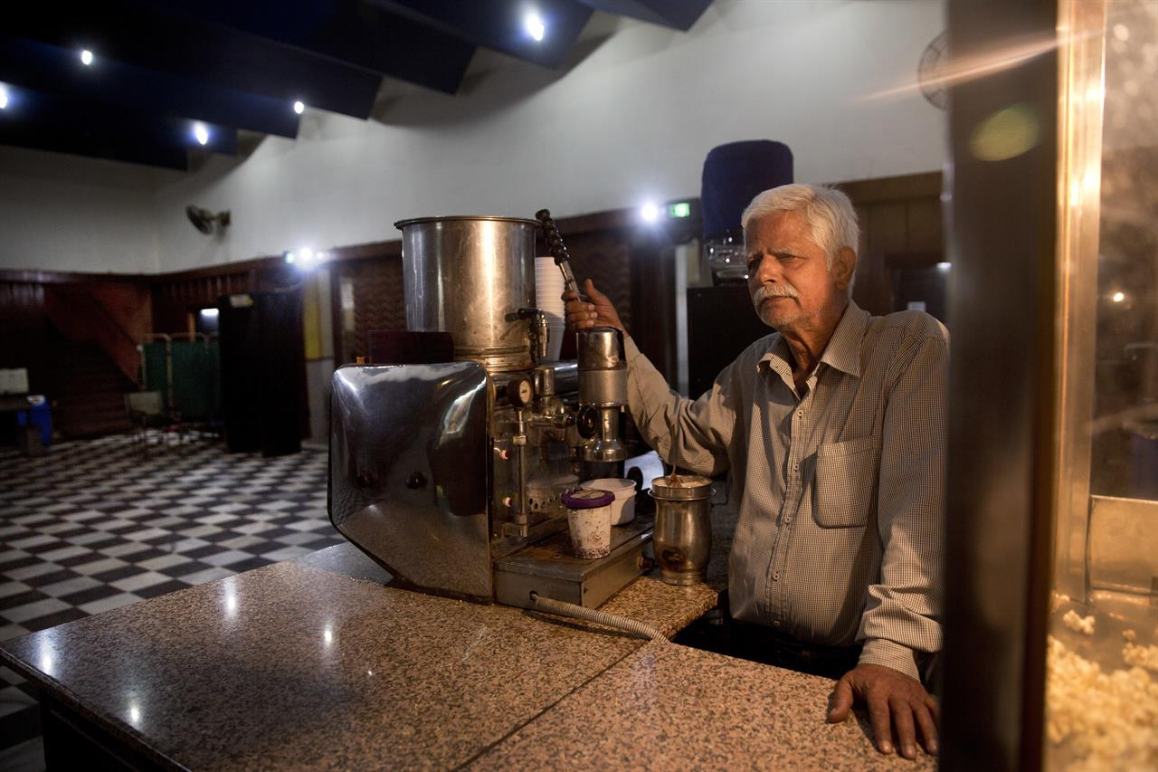In this Wednesday, March 29, 2017 photo, Joginder Singh, 72, stands next to his old expresso coffee machine and waits for customers at Regal Theater in New Delhi, India. The Indian capital's iconic theater signed off on Thursday night after more than eight decades with nearly 600 movie buffs cheering a 1964 Bollywood classic at a final screening. It's expected to make way for a multiplex from a single screen.