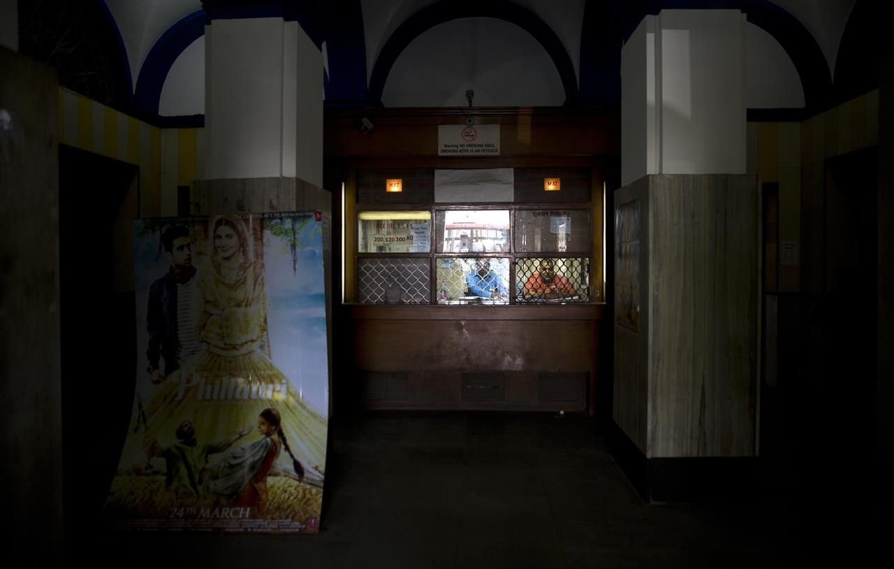 In this Tuesday, March 28, 2017 photo, employees sit at a ticket counter of Regal Theater in New Delhi, India. The Indian capital's iconic theater signed off on Thursday night after more than eight decades with nearly 600 movie buffs cheering a 1964 Bollywood classic at a final screening. It's expected to make way for a multiplex from a single screen.