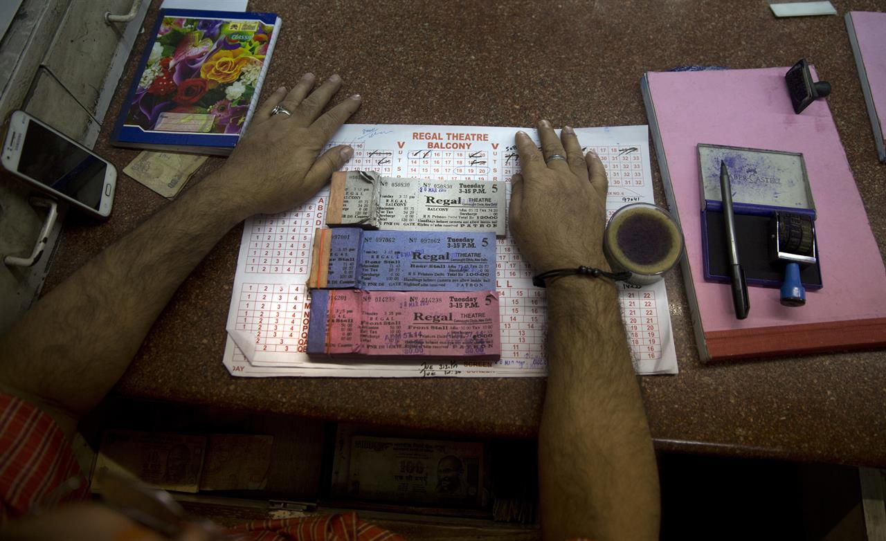 In this Tuesday, March 28, 2017 photo, a man selling movie tickets waits for customers at a ticket counter of Regal Theater in New Delhi, India. The Indian capital's iconic theater signed off on Thursday night after more than eight decades with nearly 600 movie buffs cheering a 1964 Bollywood classic at a final screening. It's expected to make way for a multiplex from a single screen.