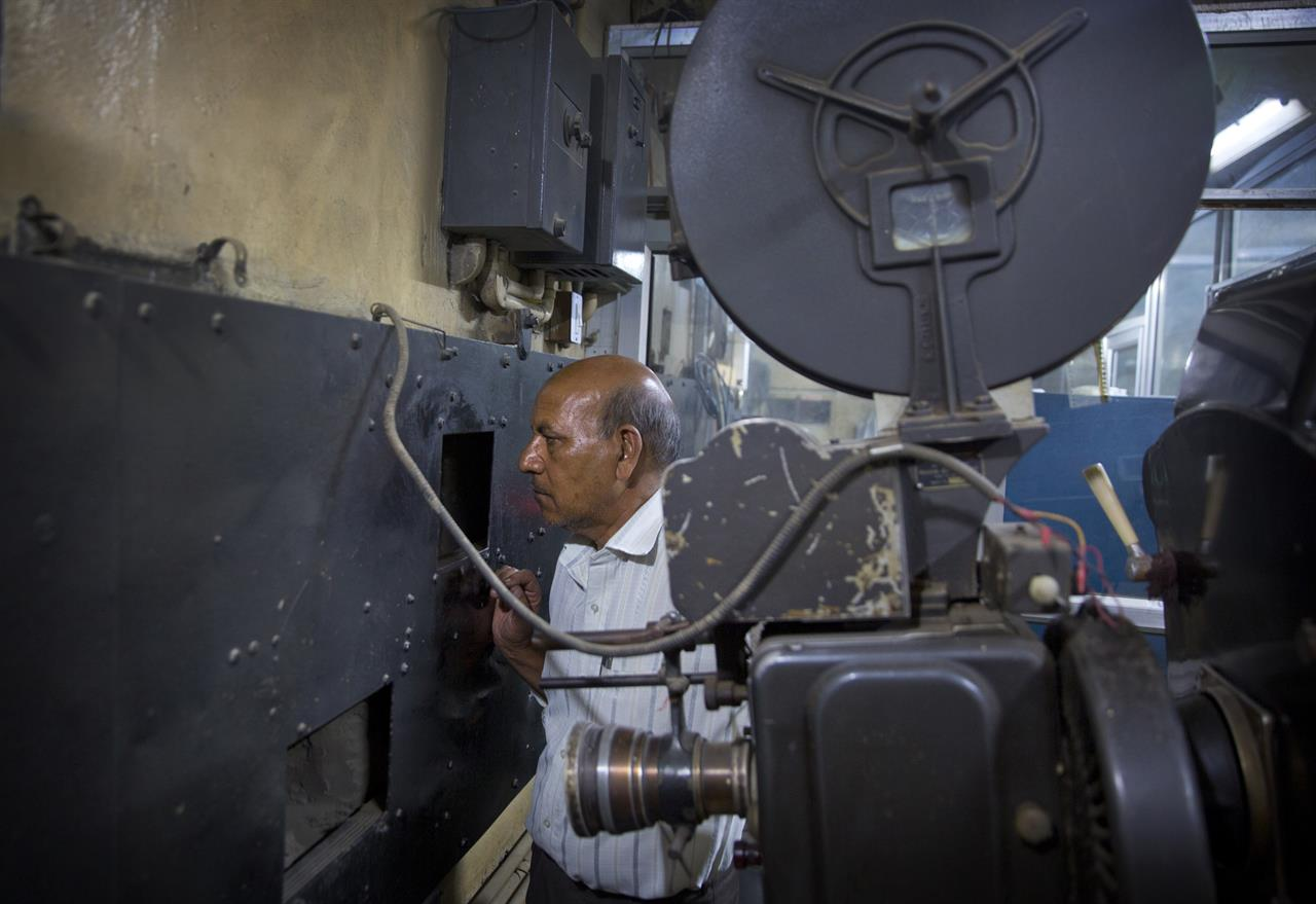 In this Wednesday, March 29, 2017 photo, Ramesh Kumar Saha, a technician in a projection room for the last 22 years, checks the playing of a Bollywwod movie, next to a 1949 film projector at Regal Theater in New Delhi, India. The Indian capital's iconic theater signed off on Thursday night after more than eight decades with nearly 600 movie buffs cheering a 1964 Bollywood classic at a final screening. It's expected to make way for a multiplex from a single screen.