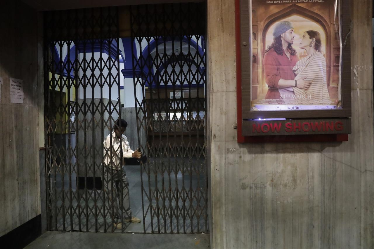 In this early Friday, March 31, 2017 photo, a guard locks the gate after the last movie screening at iconic Regal Theater in New Delhi, India. From Bollywood superstars to political heavyweights, the theater had hosted some of India's biggest names over more than eight decades. But with nostalgic theater-goers singing their way to the exits after a final showing of a Bollywood classic, the New Delhi theater has closed its doors to make way for a multiplex.