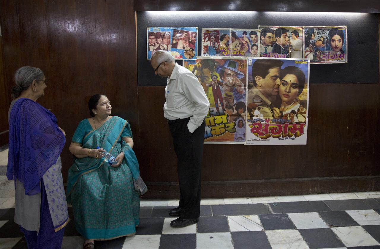 In this Wednesday, March 29, 2017 photo, elderly Indians arrive to watch the last movie screening at Regal Theater in New Delhi, India. With its corridors studded with black-and-white images of Bollywood stars such as Nargis, Madhubala, Meena Kumari, Dev Anand and Raj Kapoor, the magic of a bygone era was visible throughout the theater. From Bollywood superstars to political heavyweights, the theater had hosted some of India's biggest names over more than eight decades. But with nostalgic theater-goers singing their way to the exits after a final showing of a Bollywood classic, the iconic New Delhi theater has closed its doors to make way for a multiplex.