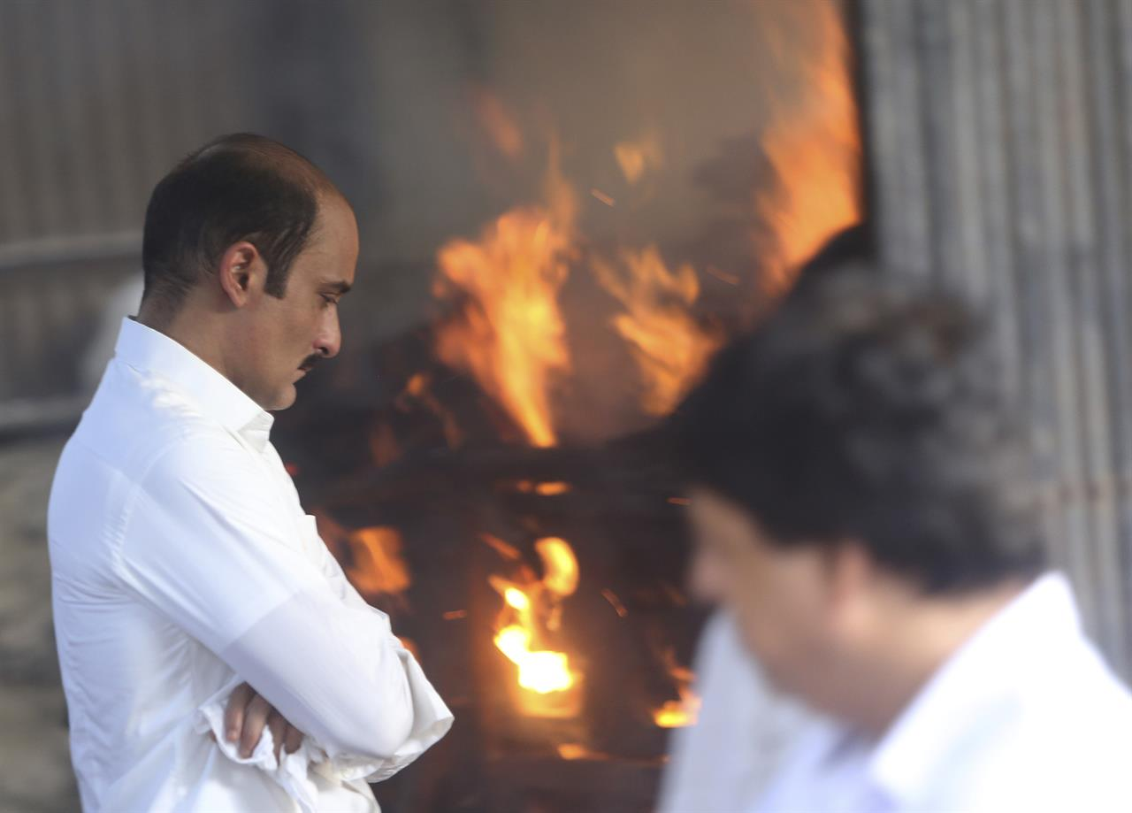 Bollywood actor Akshaye Khanna, left, son of Bollywood actor turned politician Vinod Khanna stands near his father's funeral pyre in Mumbai, India, Thursday, April 27, 2017. Khanna died of cancer on Thursday, a hospital official said. He was 70.
