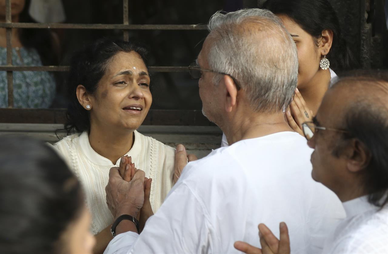 Kavita Khanna, wife of Bollywood actor turned politician Vinod Khanna is consoled by Indian film maker and poet Gulzar, back to camera during Khanna's funeral in Mumbai, India, Thursday, April 27, 2017. Khanna died of cancer on Thursday, a hospital official said. He was 70.