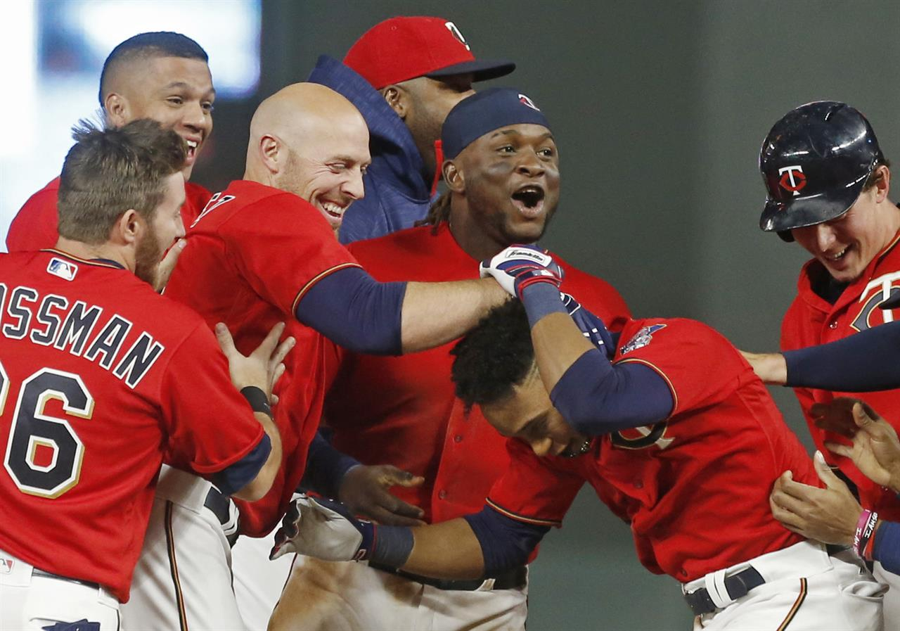 Minnesota Twins Jorge Polanco Right Is Swarmed By Teammates After His Walk Off Sacrifice Fly In The 10th Inning Of A Baseball Game Against Kansas