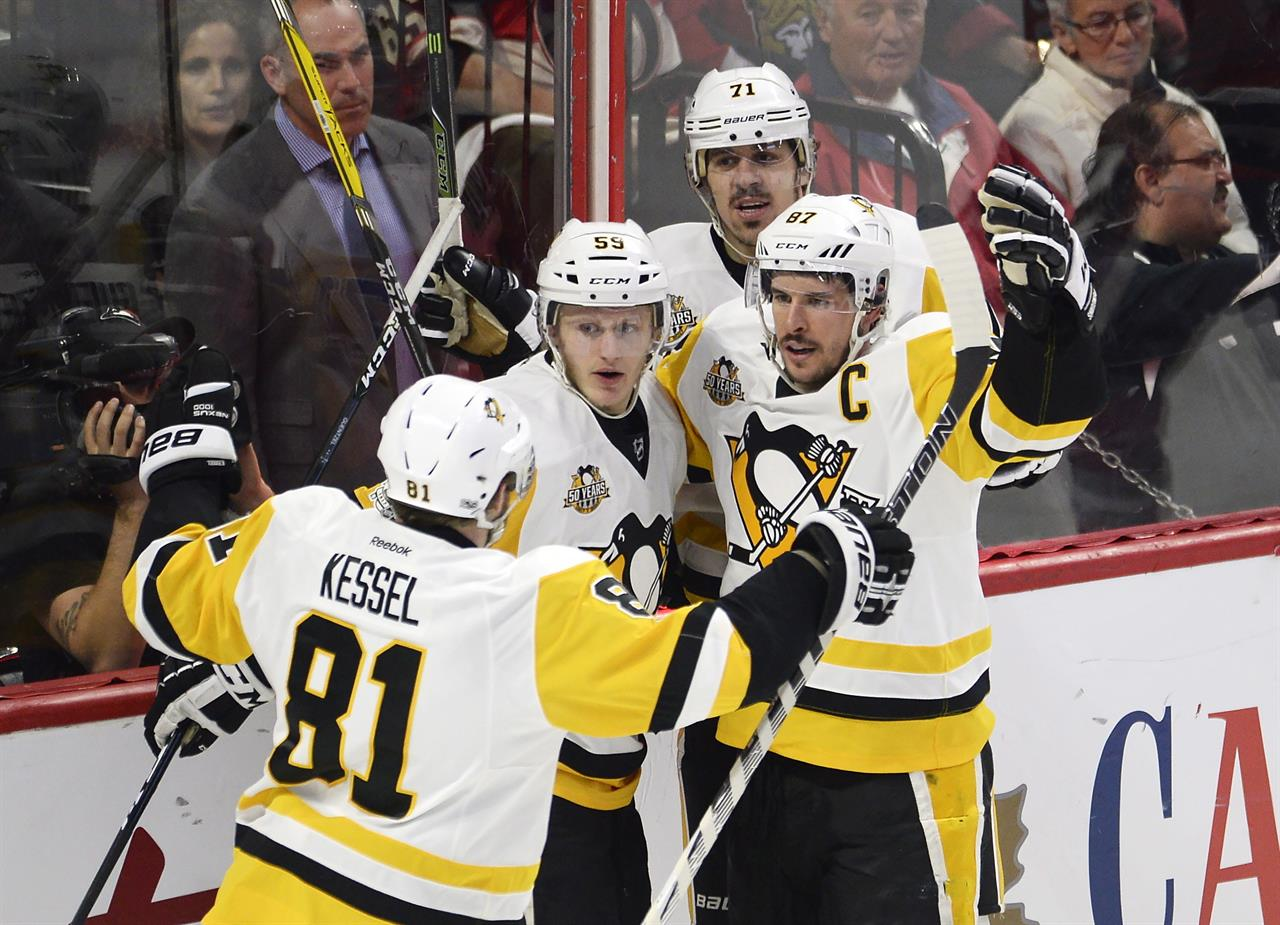 c10b31f183b Pittsburgh Penguins center Sidney Crosby (87) celebrates his goal against  the Ottawa Senators with teammates Phil Kessel (81)