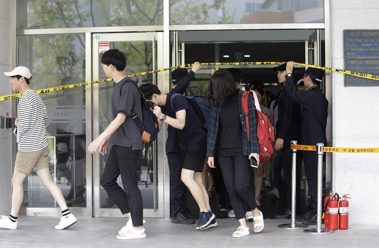 Students come out of an engineering faculty building at Yonsei University in Seoul, South Korea, Tuesday, June 13, 2017. A South Korean professor in the mechanical engineering department was injured Tuesday after opening a concealed explosive device brought to his university office in Seoul, police said. (AP Photo/Ahn Young-joon)