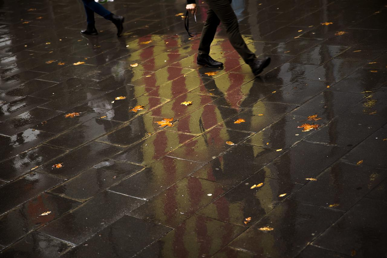 People walk past a Catalan flag reflected on the ground in Barcelona, Spain, Thursday, Oct. 19, 2017. Spain's government on Thursday immediately rejected a threat by Catalonia's leader to declare independence unless talks are held, calling a special Cabinet session for the weekend to activate measures to take control of the region's semi-autonomous powers. (AP Photo/Emilio Morenatti)